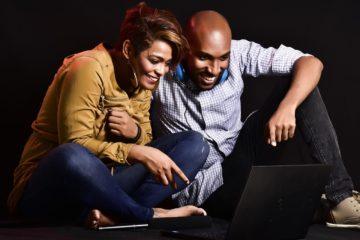 couple riant devant un écran d'ordinateur